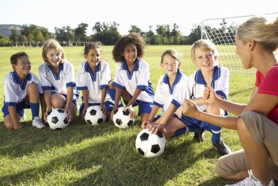 A group of kids sitting on ground and holding football