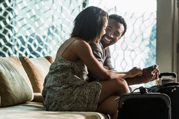 A couple sitting on a sofa in front travel bags